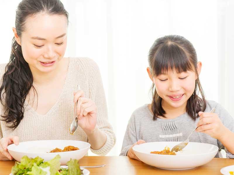 カレーライスを食べる親子