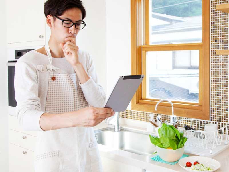 台所でレシピを見る夫