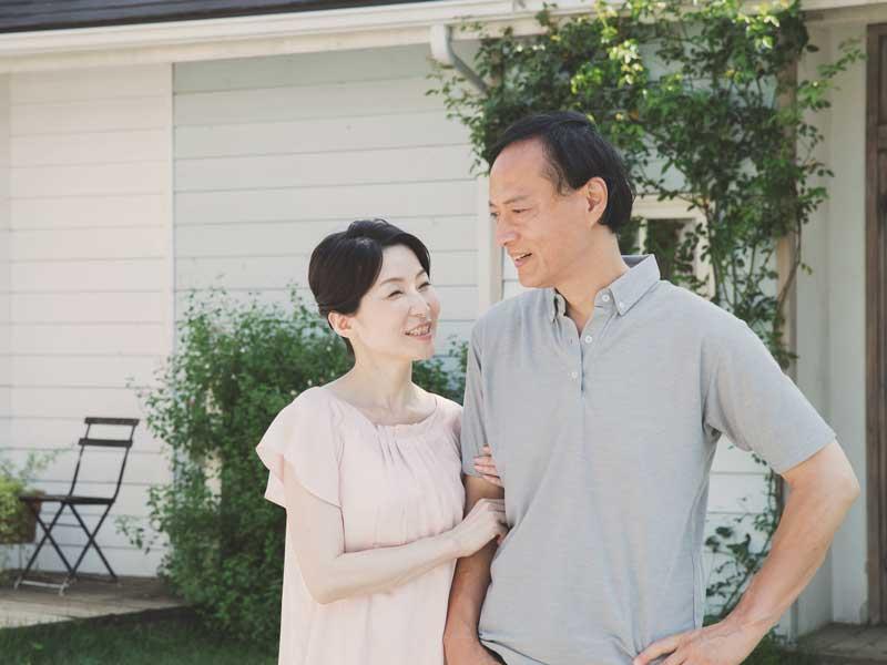 家の前に立つ銀婚式を迎えた夫婦