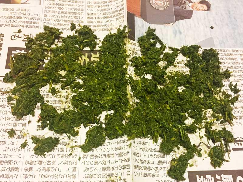天日干しするために新聞紙に広げられた茶殻 class=