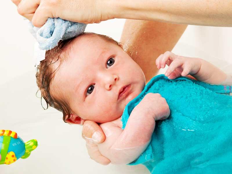 沐浴をしている新生児