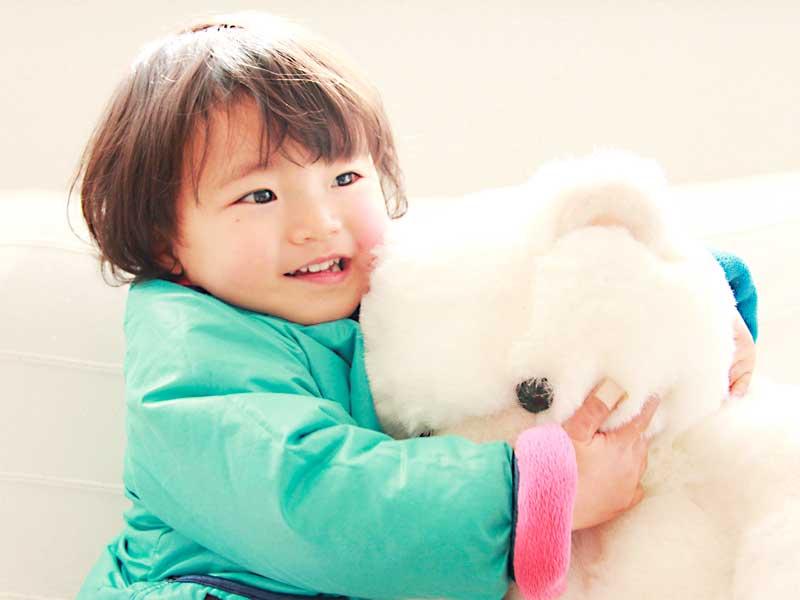 ぬいぐるみを抱っこする二歳児