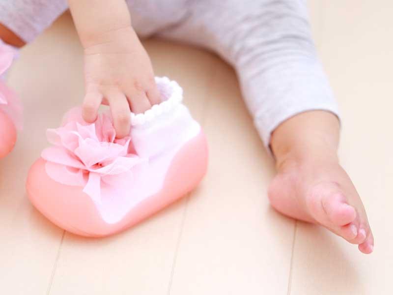 自分で靴を履こうとしている女の子の手