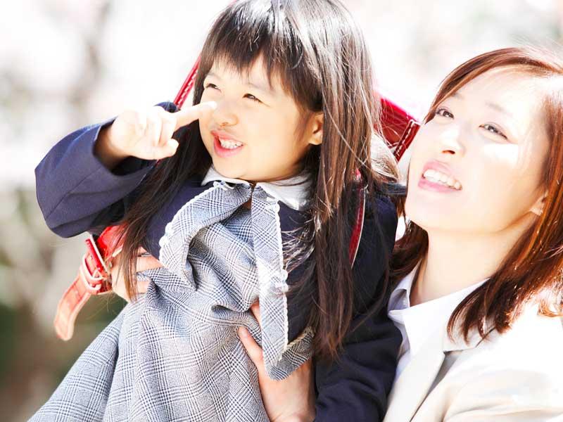 桜の木を見上げるランドセルを背負った女の子とママ