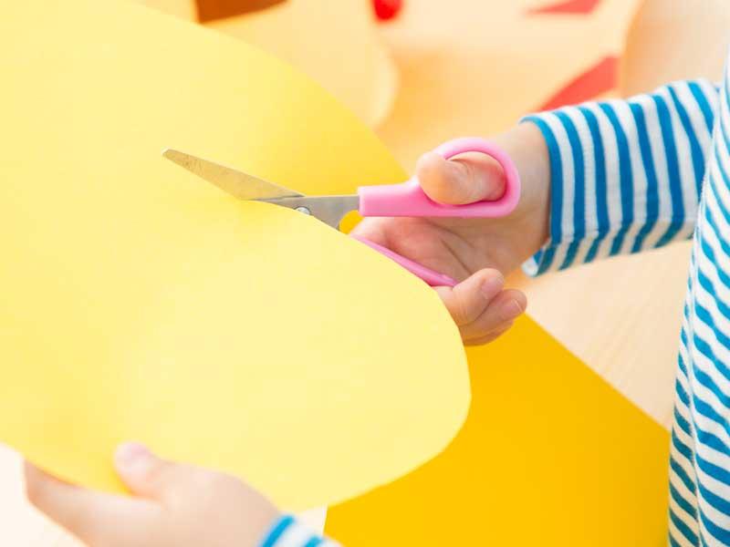 はさみで紙を切る子供の手