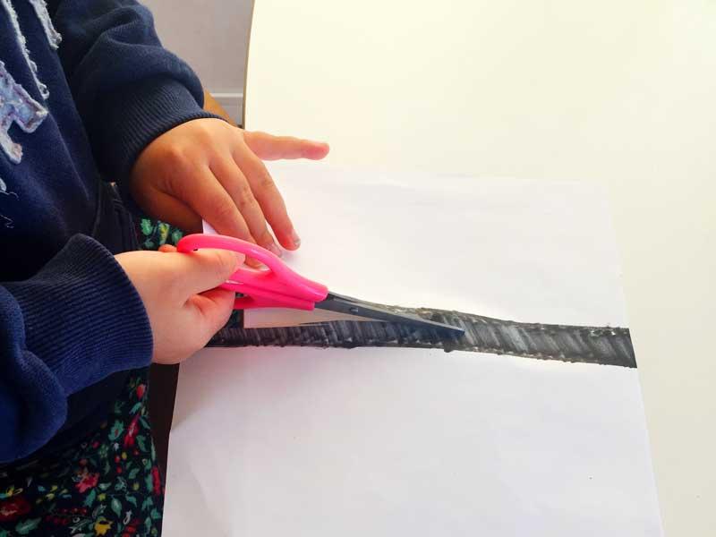 ハサミで紙を切る練習をしている子供