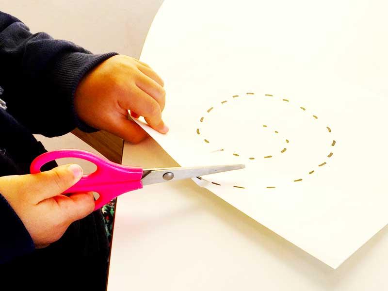 紙を動かしてハサミで切る子供