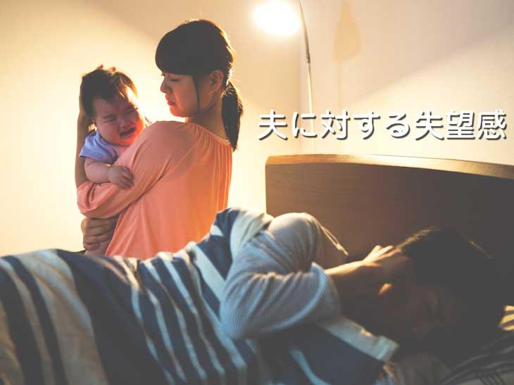 夜泣きする赤ちゃんを抱っこしているママに背を向けて寝てるパパ