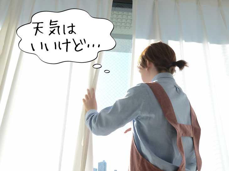 カーテンを開けて外を見ているお母さん