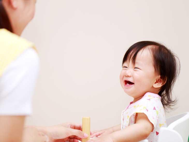 先生と遊ぶ笑顔の赤ちゃん