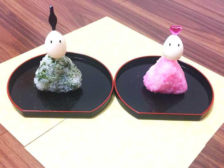 オニギリの上に黒ゴマでうずらの卵を顔に見立てて載せて作ったお雛様とお内裏様