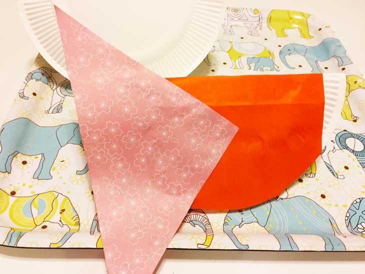 折り紙を張って体の部分の飾り付けをしている紙皿