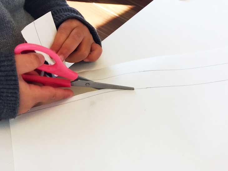 画用紙で2枚の細長い紐を子供が切っている様子