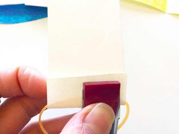 片側に輪ゴムをかけてホチキスで留めた細い画用紙