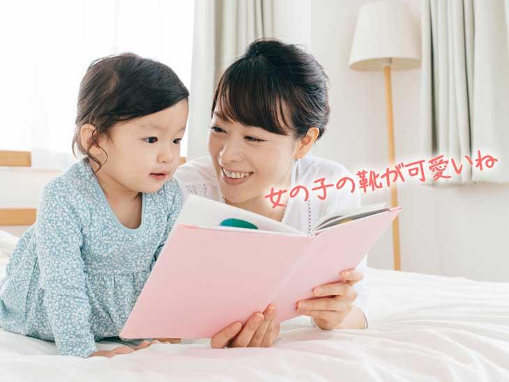 赤ちゃんに絵本を読むママ