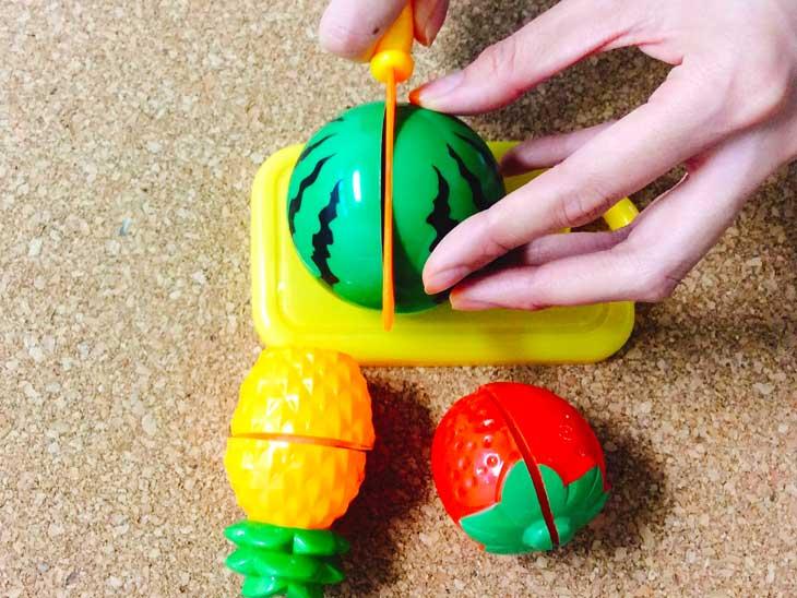 おもちゃのスイカにおもちゃの包丁を差し込む
