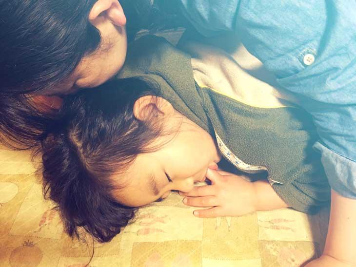 幼児の頭の匂いを嗅ぐ母親