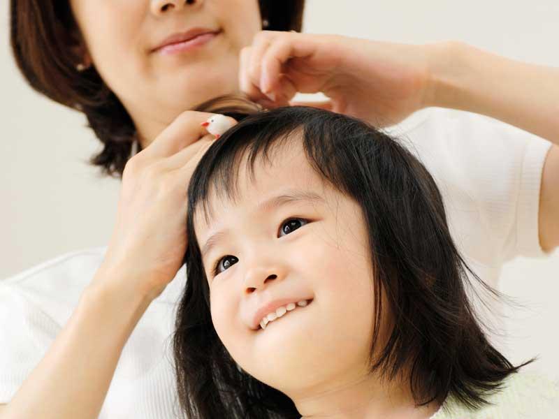 子供の髪をセットしてあげているお母さん