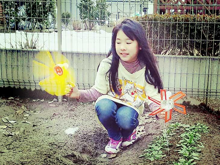 ペットボトルで作った風車を外で回している女の子