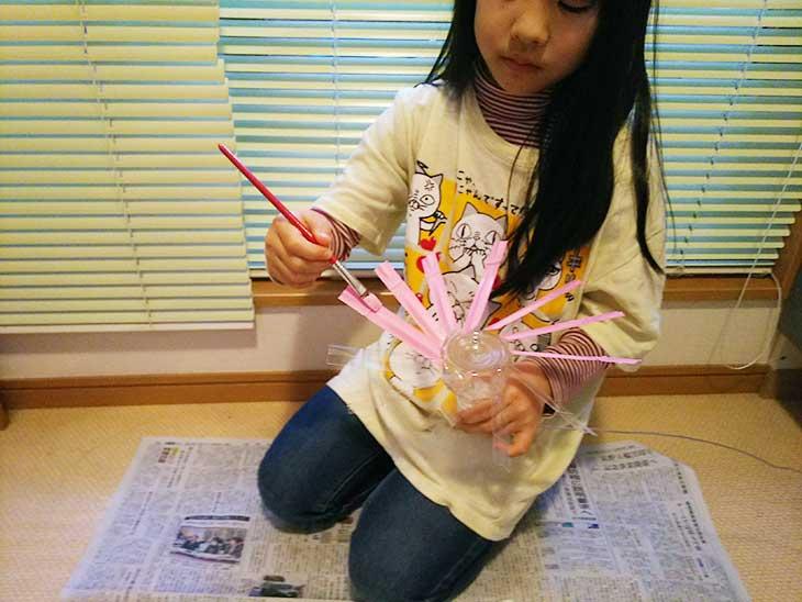 アクリル絵の具でペットボトル風車の羽根に色を塗っている女の子