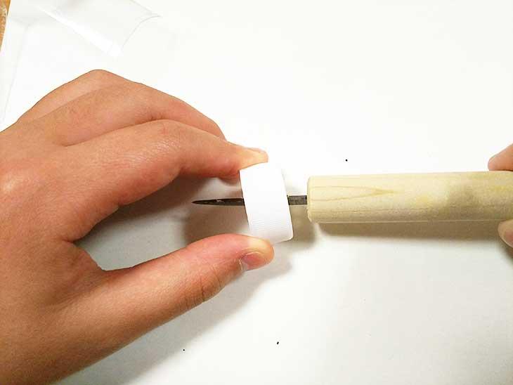 キリの根本まで使ってシッカリと穴を開けられたペットボトルのキャップ