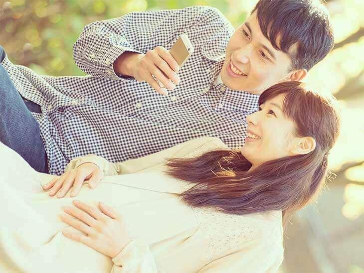 スマホのアプリを見ている妊婦さんとその旦那さん