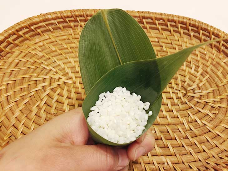 三角錐の形に折り込んだ笹の葉にもち米を入れる