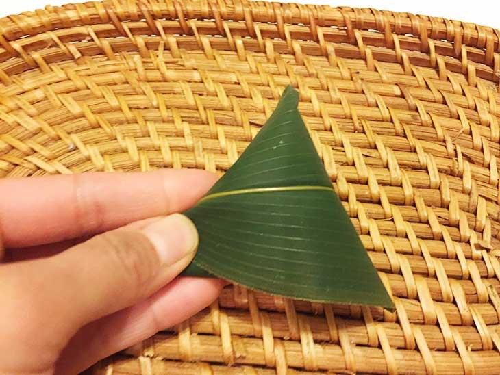 もち米を入れた笹の葉を織り込んで蓋をする
