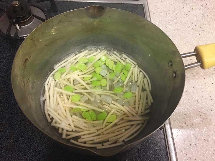 鍋でうどんと枝豆を茹でる