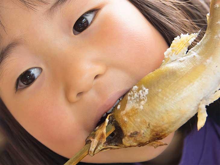 焼き魚を丸かじりしている女の子