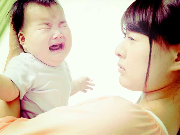 抱っこしても泣き止まない赤ちゃんを見て困っている母親