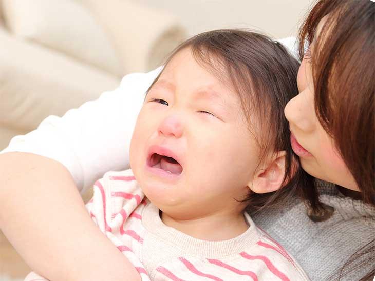 母親に抱っこされているのに泣いている女の子