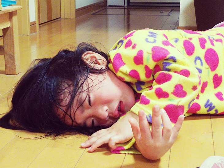 床に寝そべって泣いている女の子