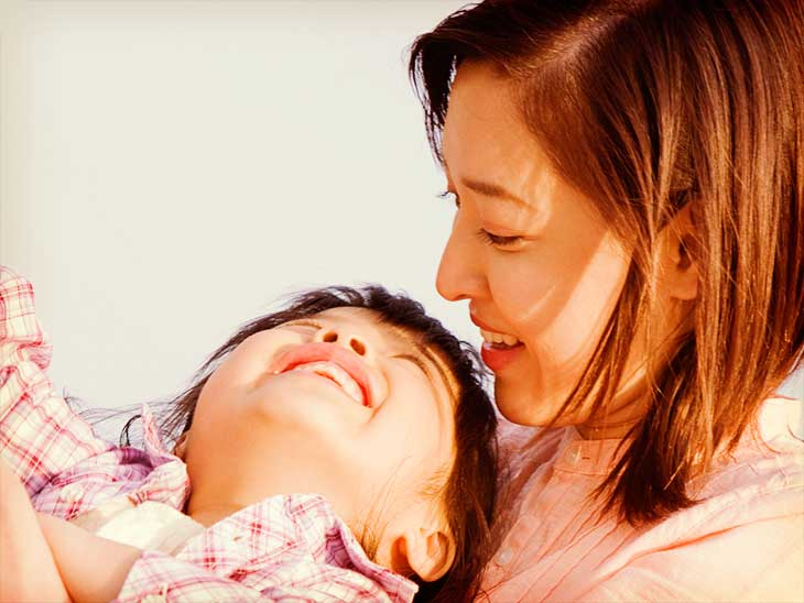 後ろから抱きついてきた母親の顔を見上げて笑顔の男の子