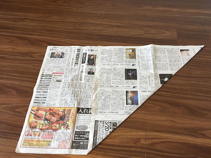 広げた新聞紙の短辺を長辺に合わせて折った写真