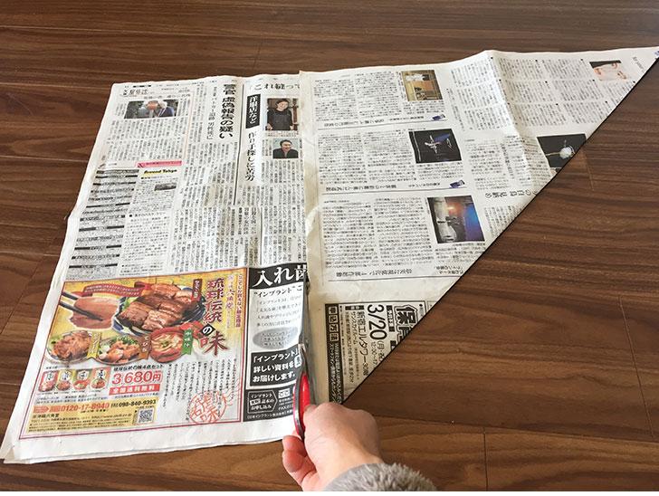 新聞紙が重ならない部分をハサミで切る様子