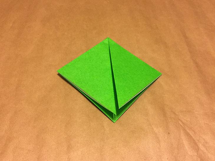 三角に折った紙の左右の角を下の頂点に向かって折った写真
