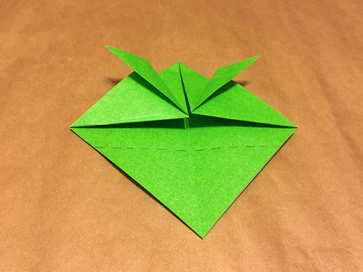 上部点線で折りられ中央に点線が書かれた折り紙の写真