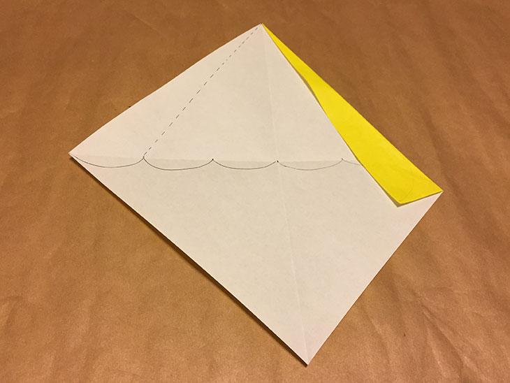 点線や印に合わせて上部左側が折られた折り紙の写真