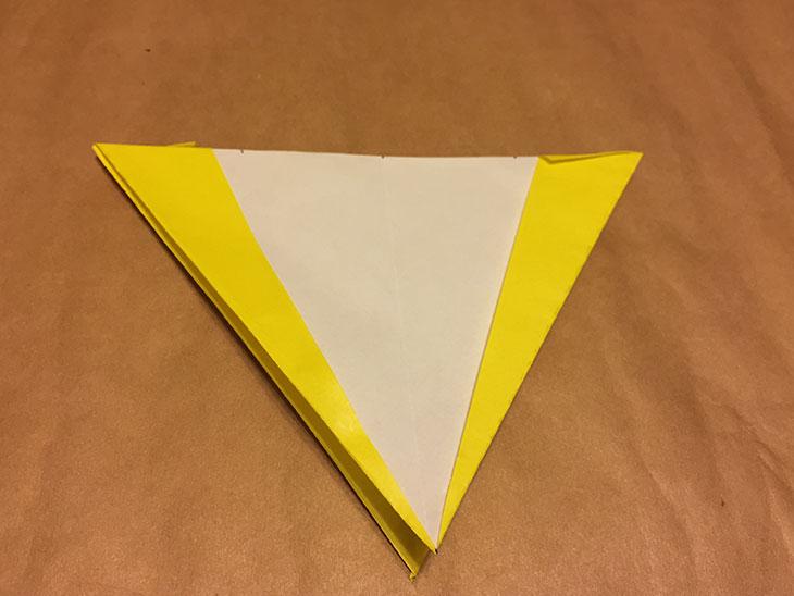 上下左右を折って裏返して縦半分に折った折り紙の写真