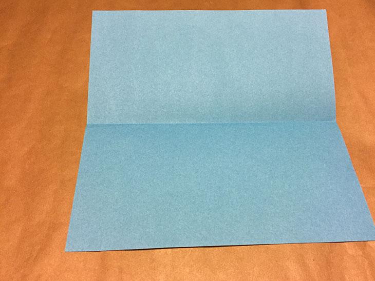 青い折り紙の中央に折り目がついている写真