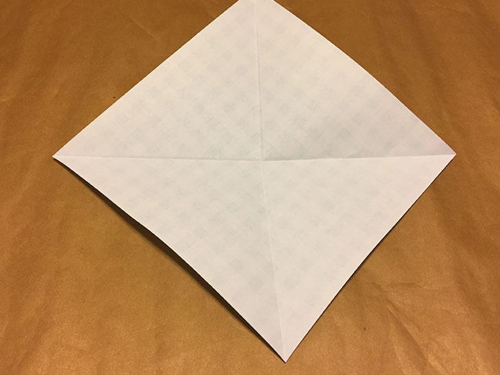 対角線に折り目をつけた白い面の折り紙の写真