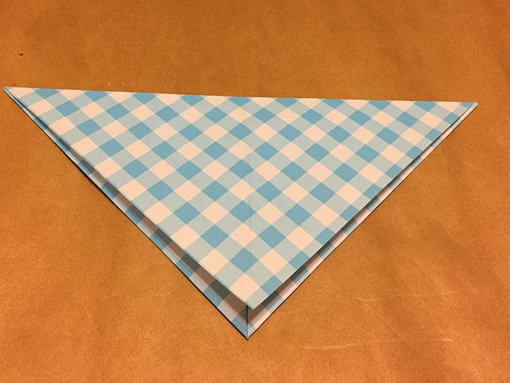 上の頂点を下の頂点に合わせて三角に折った折り紙の写真