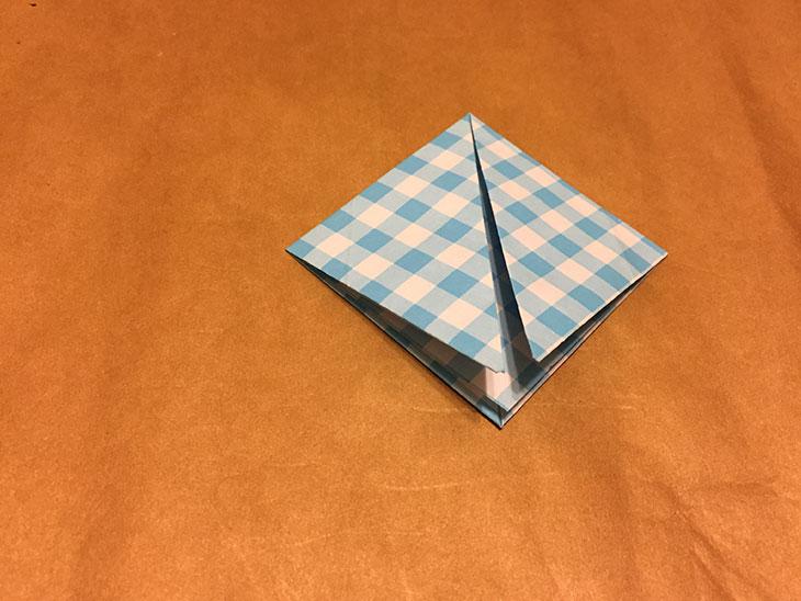 左右の頂点を下の頂点に重ねて折った折り紙の写真