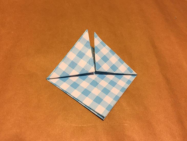 上に重ねて折った部分を半分折り上げた折り紙の写真