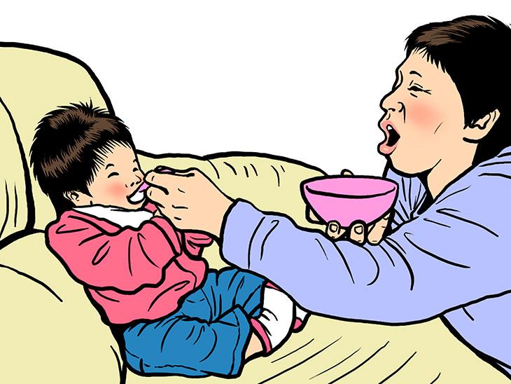 ソファーでご飯を食べさせてもらっている赤ちゃん