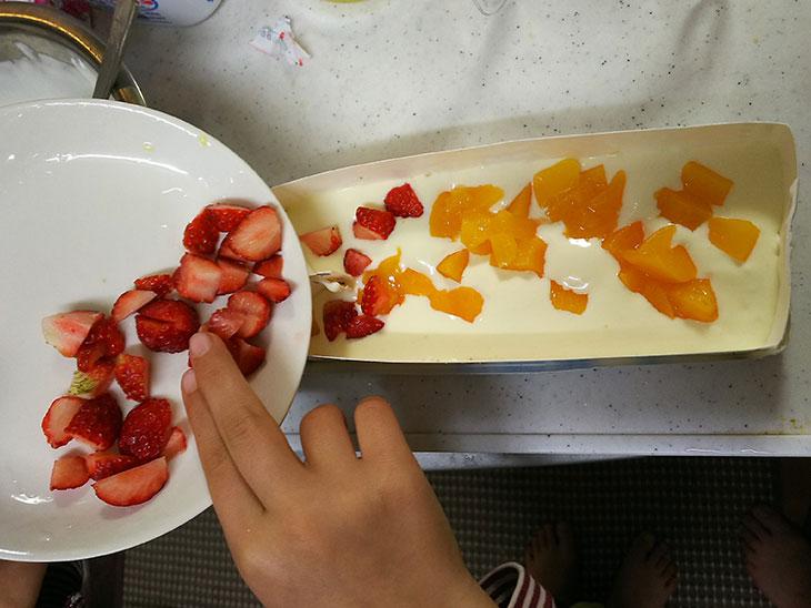 アイスの元を型に流し込みフルーツトッピングする様子