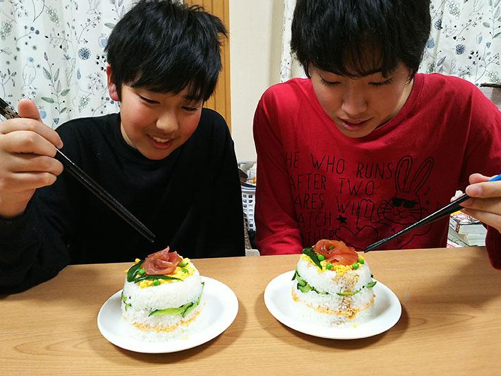 完成したこどもの日のお寿司ケーキを食べる笑顔の男の子達の写真