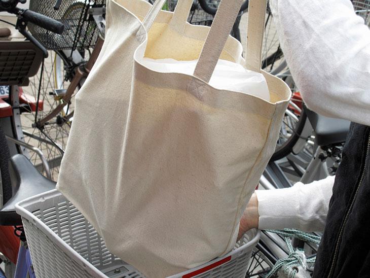 自転車のカゴに買い物バッグを入れる女性