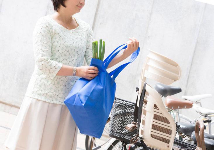 買い物バッグを持つ女性と自転車